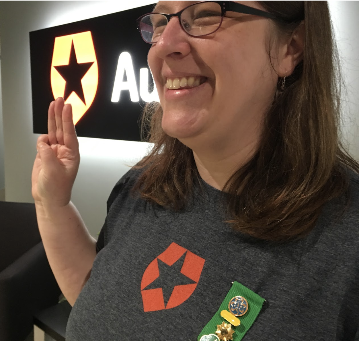 Auth0 Support Operations Manager Abigail Sanchez showing Scout Sign Salute with badges of Scout accomplishments
