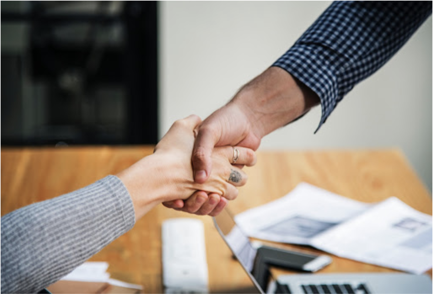 Two people shaking hands in office environment