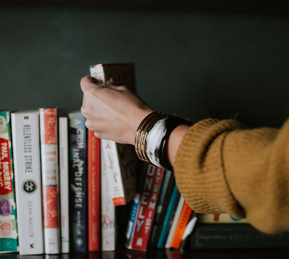 A picture of diffrent books and a hand holding one